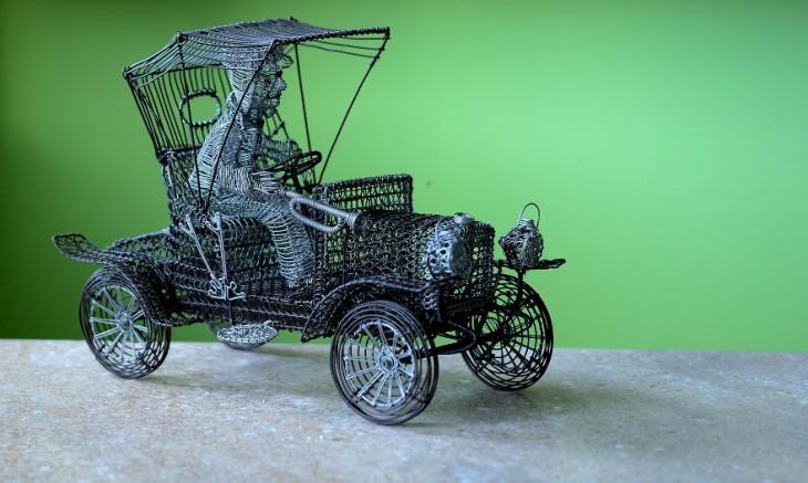 Escultura de alambre con forma de un carrito con un chofer