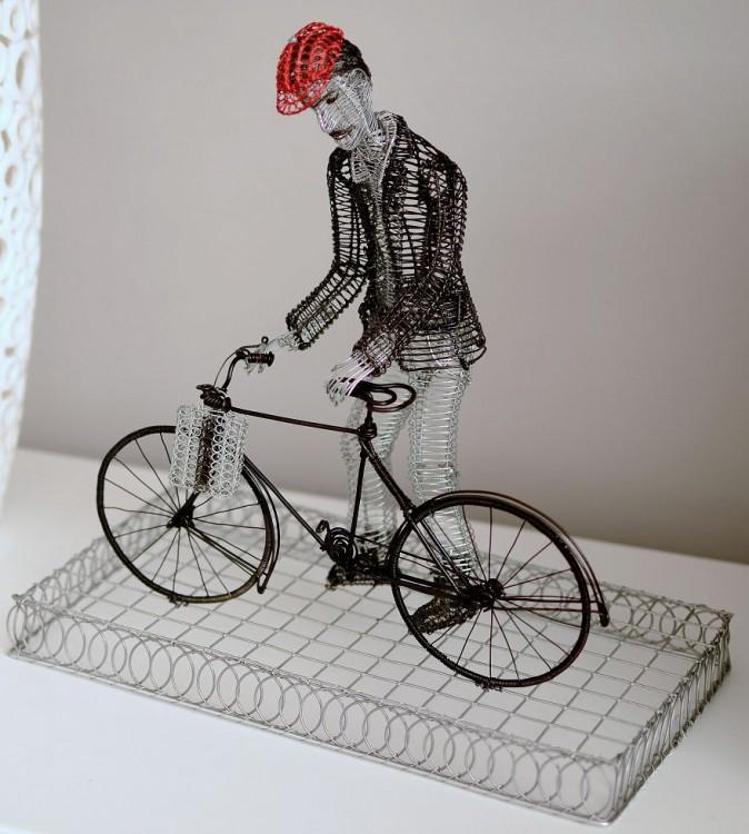 Escultura de alambre con figura de un hombre en su bicicleta