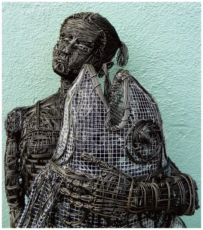 Escultura de alambre de una chica con un pescado en la mano por Zak Gere