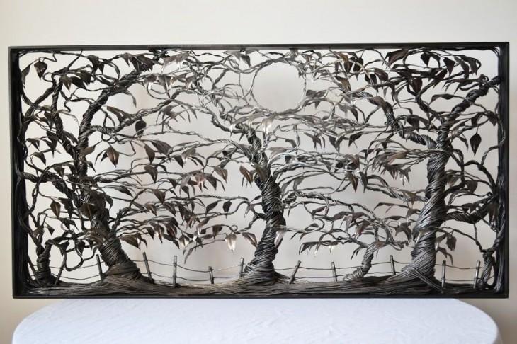 Escultura de alambre que simula un bosque con una luna