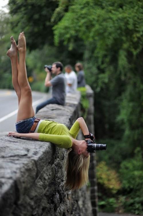 Fotógrafa acostada y de cabeza en una piedra