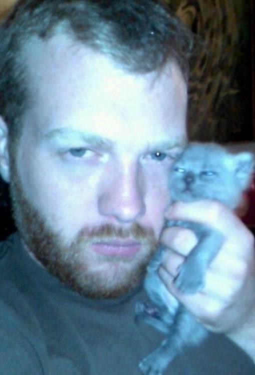 Cara de un hombre cargando un pequeño gato a su lado