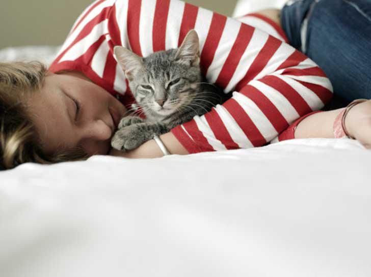 Chica acostada abrazando a un gato a un costado de ella
