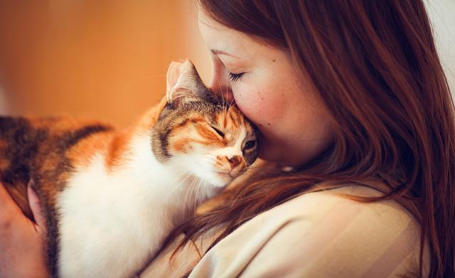 Mujer dando un beso a su gato