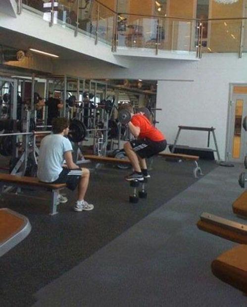 Chico en un gimnasio sobre unas pesas levantando una pesa