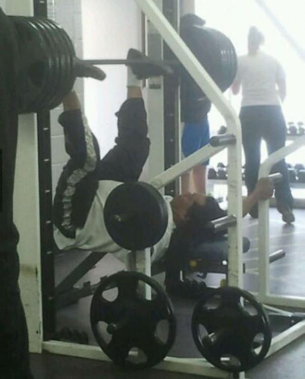 Un hombre en el gimnasio usando mal los aparatos