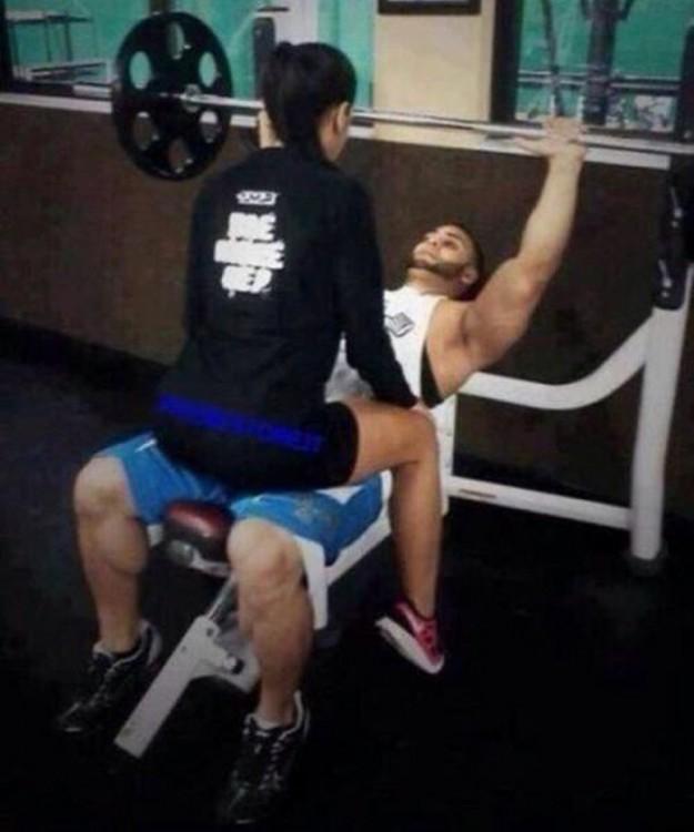 Un chico haciendo pesas con la novia sentada sobre él