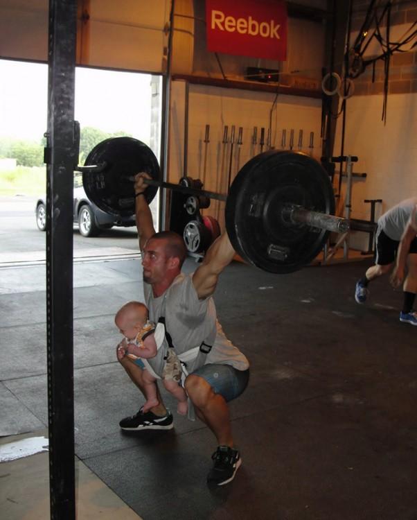 Hombre en el gimnasio con una cangurera y su bebé cargando una pesa