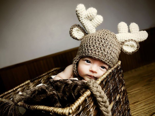 Bebé con un gorro de estambre con la forma de siervo