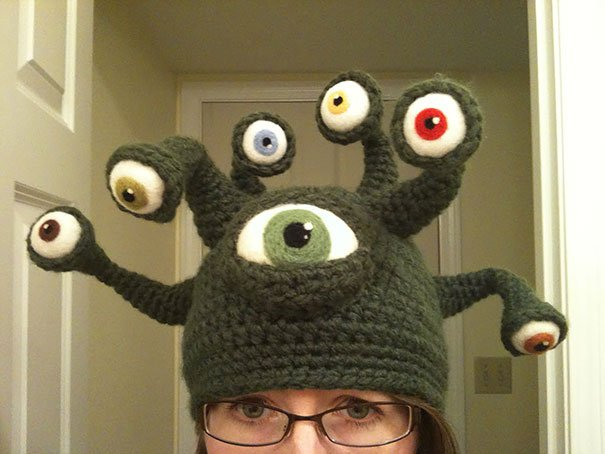 Gorro de color verde con muchos ojos sobre él