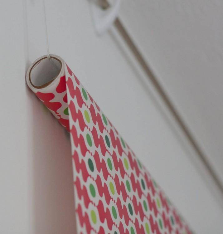 Tubo de papel en color rojo con figuras sobre una pared