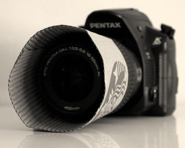 Cámara fotográfica con un cartón de café sobre su lente
