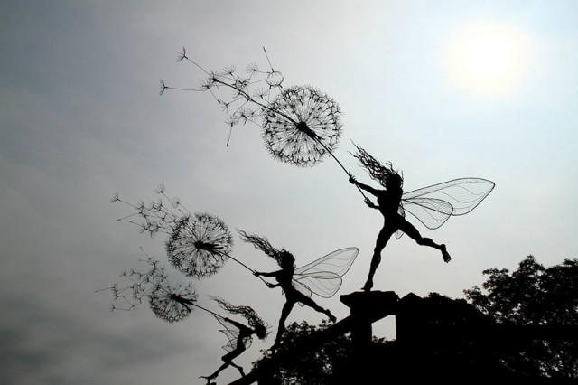 Tres esculturas de hadas sosteniendo algo en sus brazos