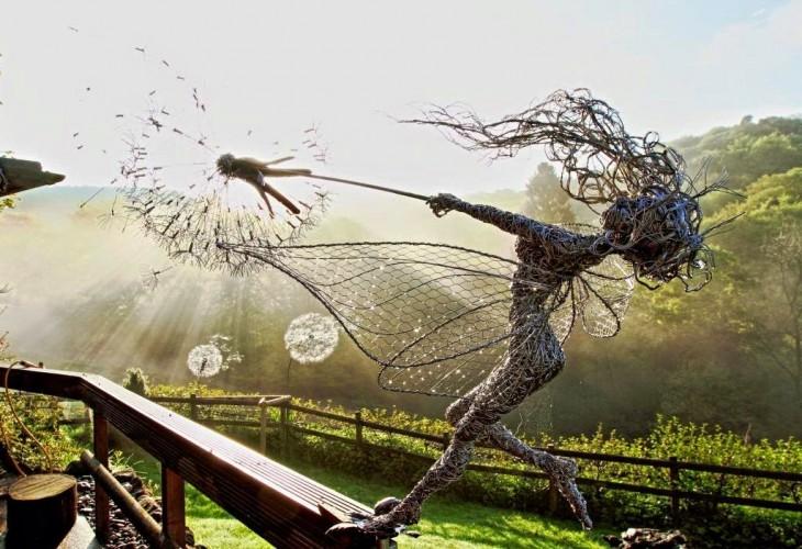 Escultura de una hada que parece estar jalando una flor