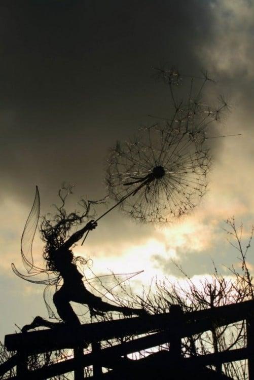 Escultura de hada a contra luz que parece estar aventando algo con su brazo