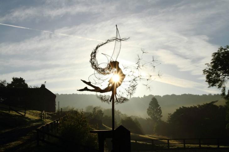 Escultura de hada a contra luz que parece estar viendo hacia arriba