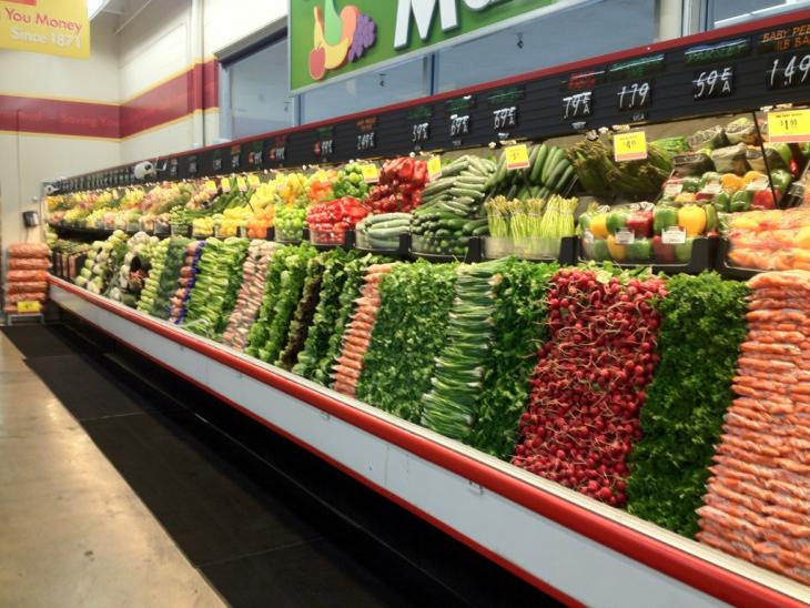 Pasillo de verduras en un supermercado ordenado por colores y verduras