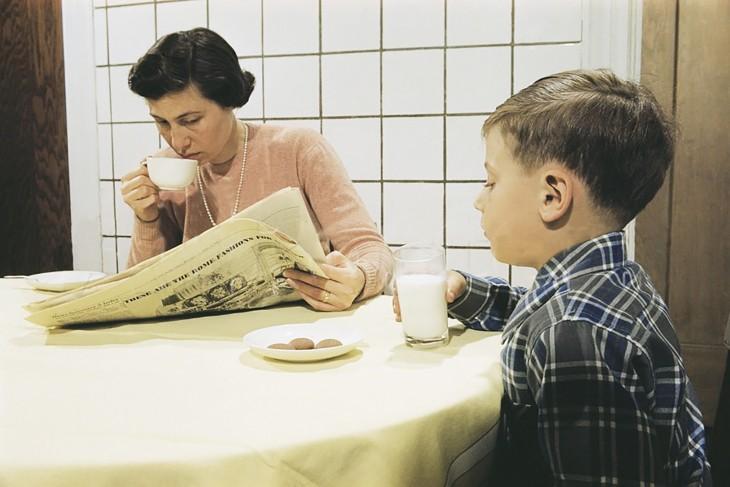 Madre con un periódico en sus manos a lado de su hijo que toma leche con galletas