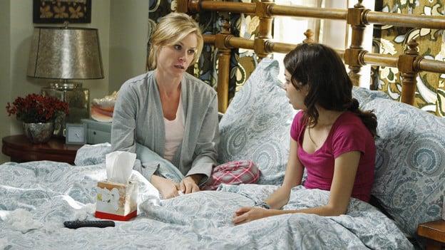 Madre junto a su hija sentadas en una cama platicando la una con la otra