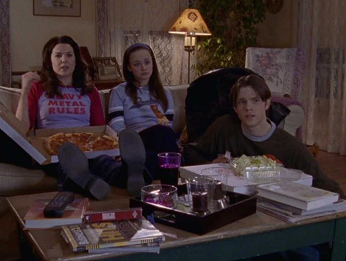 Mamá viendo películas con sus hijos en la sala de su casa