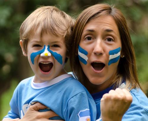 Madre a lado de su hijo vestidos con el uniforme de Argentina
