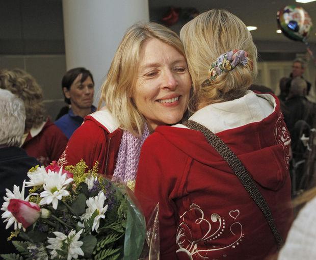 Mujer abrazando a su hija en el aeropuerto con un ramo de flores
