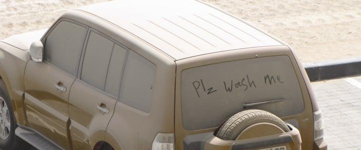 Carro demasiado sucio con un pequeño letrero en un parabrisas
