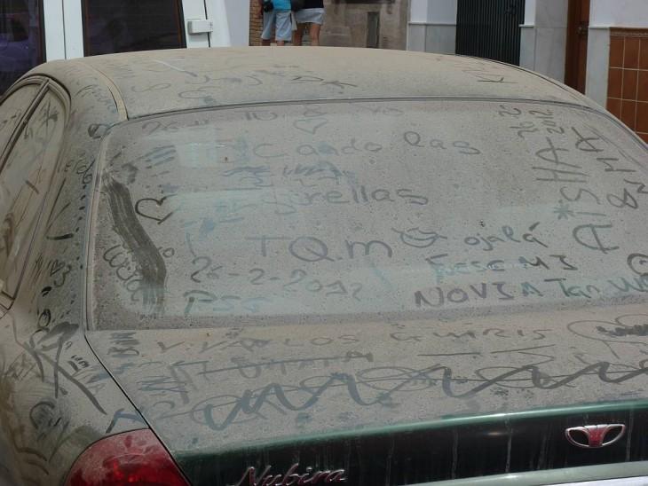 Mensajes en un parabrisas de carro lleno de tierra