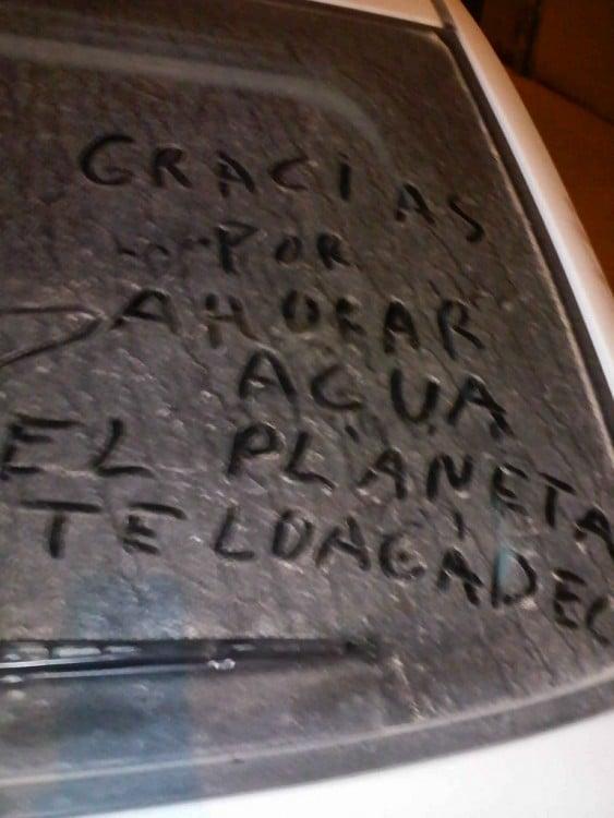 Mensaje en un parabrisas lleno de tierra que dice que gracias por ahorrar agua