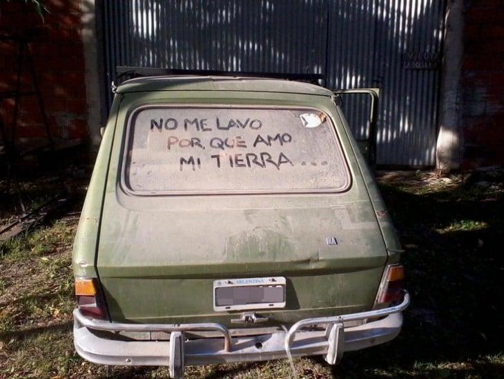 Carro con un mensaje en su parabrisas trasero lleno de tierra