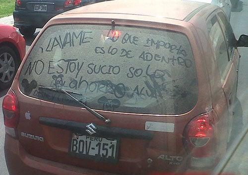 Mensaje hecho con tierra en el parabrisas trasero de un coche