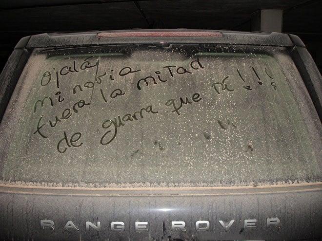Mensaje en el parabrisas de un coche lleno de tierra