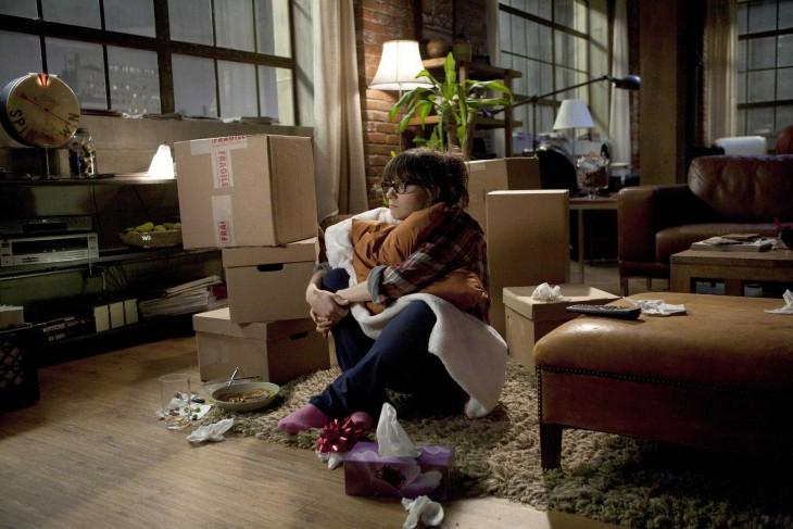 Chica sentada en el suelo de una habitación con cajas a su alrededor y abrazando algunas cosas