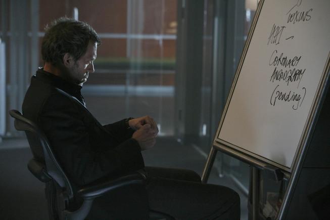Dr. House en una escena donde esta sentado en una silla de ruedas frente a una pizarra viendo fijamente.