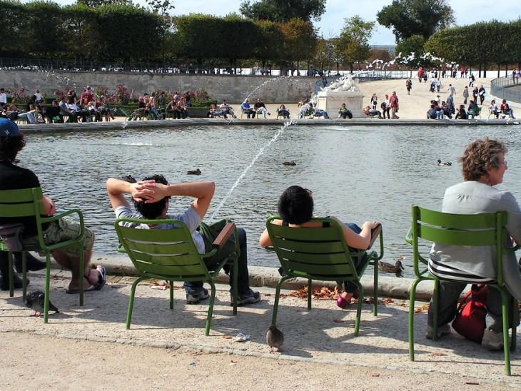 Personas sentadas a la orilla de un lago donde un chico tiene un chorro de agua frente a él