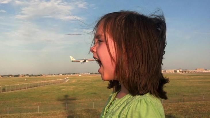 Foto tomada en el momento exacto donde un avión simula entrar a la boca de la niña