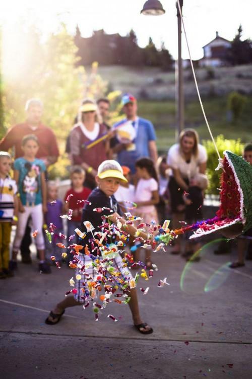 Imagen de un niño quebrando una piñata y los dulces saltando