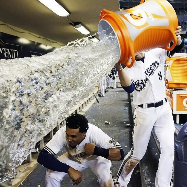 Béisbolista vaciando un garrafón de agua sobre un compañero