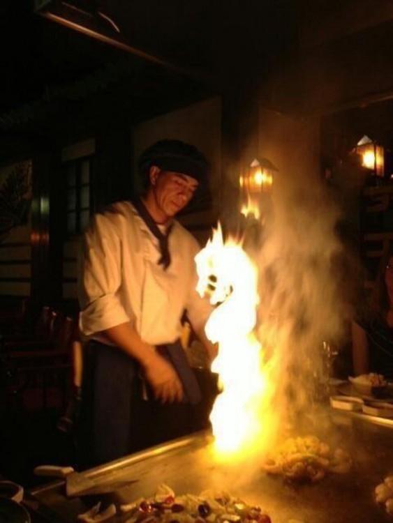Cocinero frente a una plancha donde sale un fuego en forma de dragón