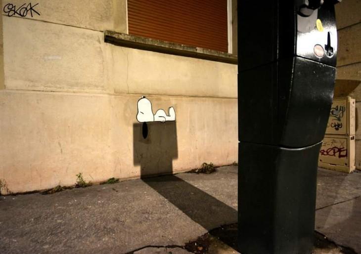 Dibujo de snoopy simulando que esta acostado sobre una sombra que parece ser una casa de perro
