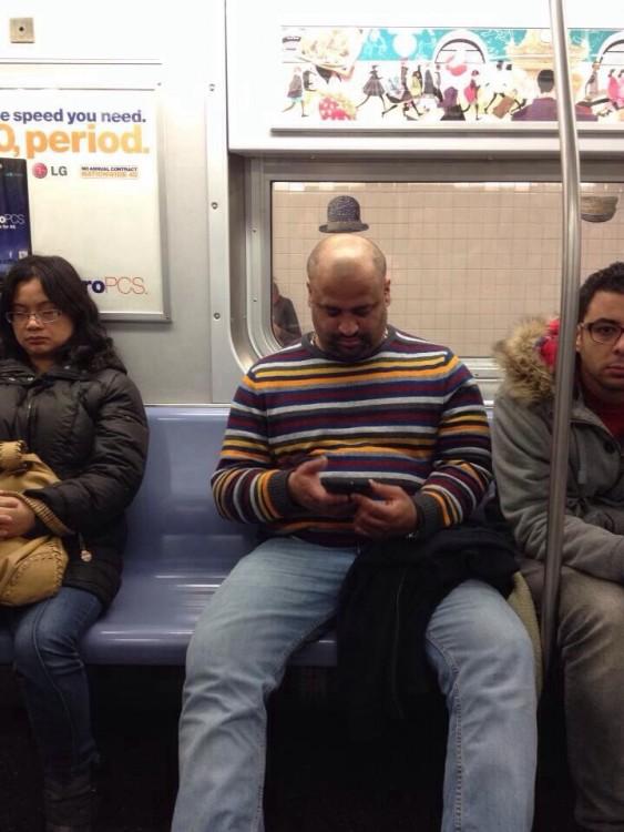 Hombre sentado en el transporte público que parece tener un sombrero sobe su cabeza
