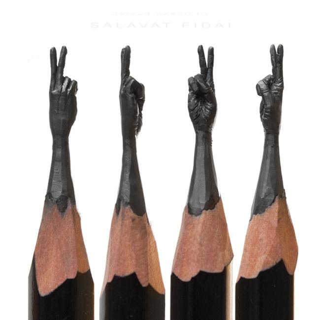 Puntas de lapices con una mano hacia arriba con dos dedos levantados