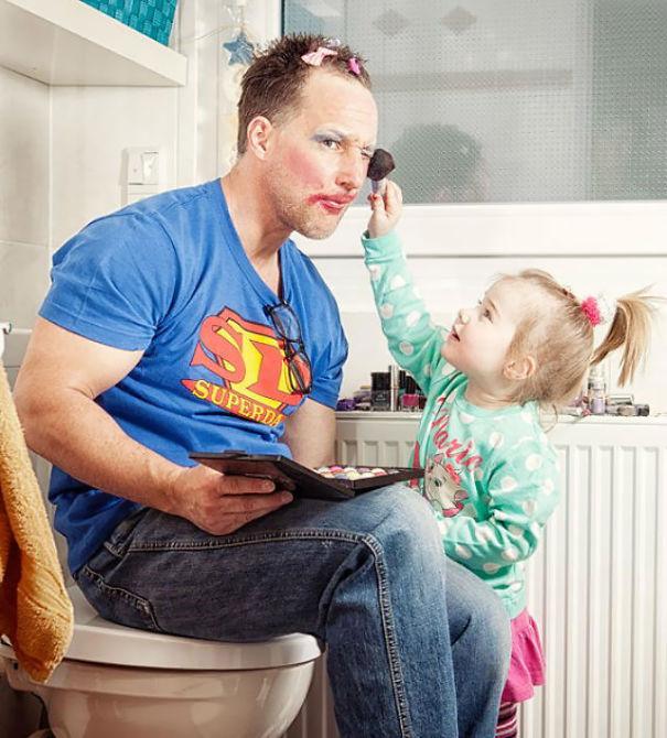 Niña maquillando la cara de su padre
