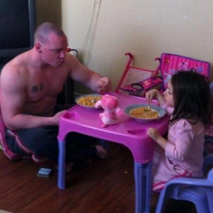 Padre e hija sentados en una pequeña mesa comiendo juntos
