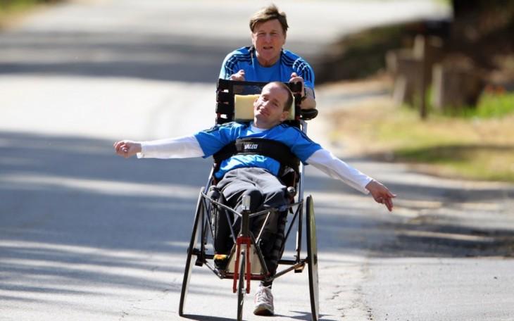 Hombre detrás de un chico empujándolo en su silla de ruedas