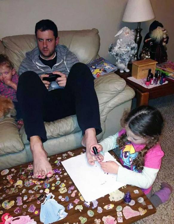 Hombre sentado en un sillón jugando videojuegos mientras su hija le pinta las uñas de los pies