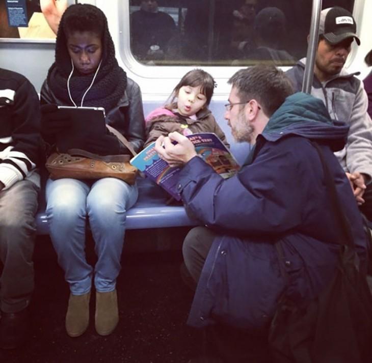 Personas en un transporte público y un padre mostrando un libro a su hija