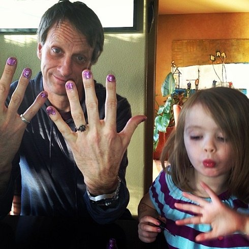 Padre con las uñas pintadas y su hija pintándose las uñas también
