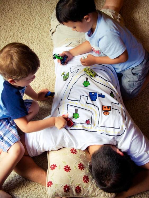 Un hombre con camisa de carretera acostado en el suelo y unos niños jugando sobre el