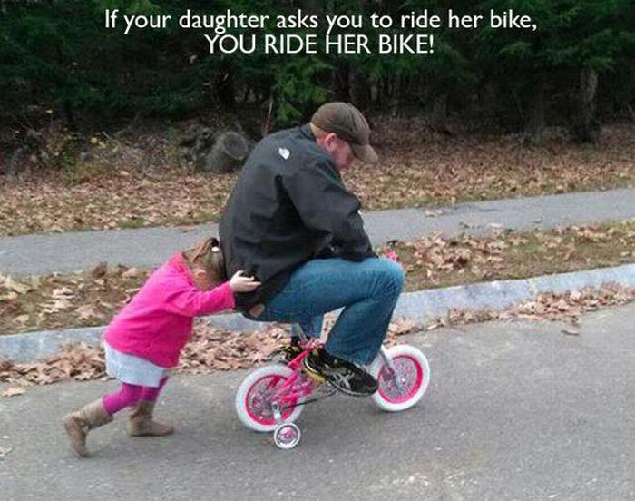 Hombre arriba de una bicicleta de niña y su hija empujándolo